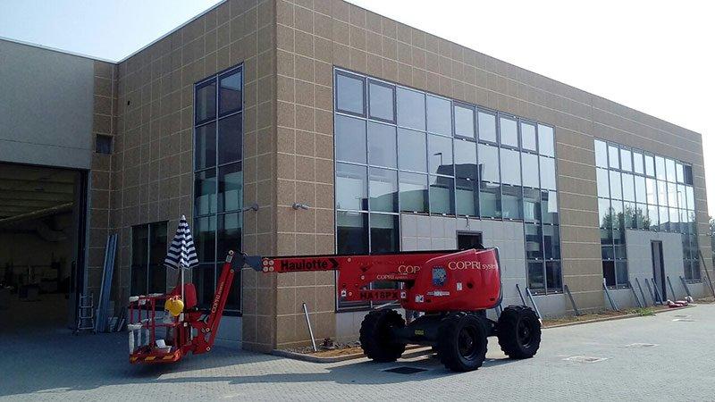 Facciata di un capannone industriale con gru rossa nelle vicinanze