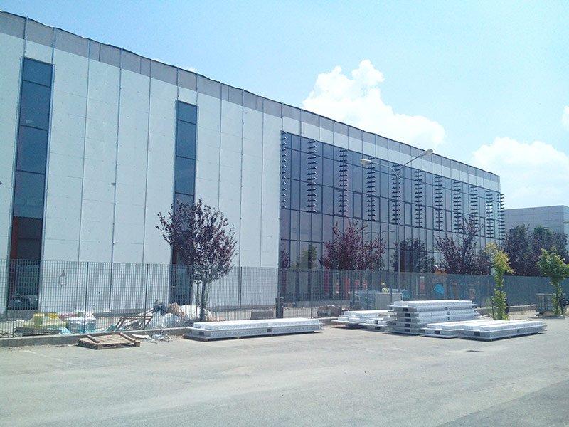 Facciata di un capannone industriale bianco con vetri a specchio