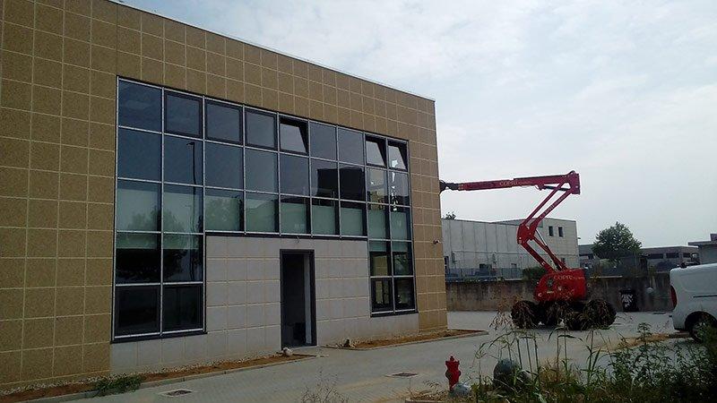 Facciata di un capannone industriale con vetrate a specchi e una gru rossa nelle vicinanze