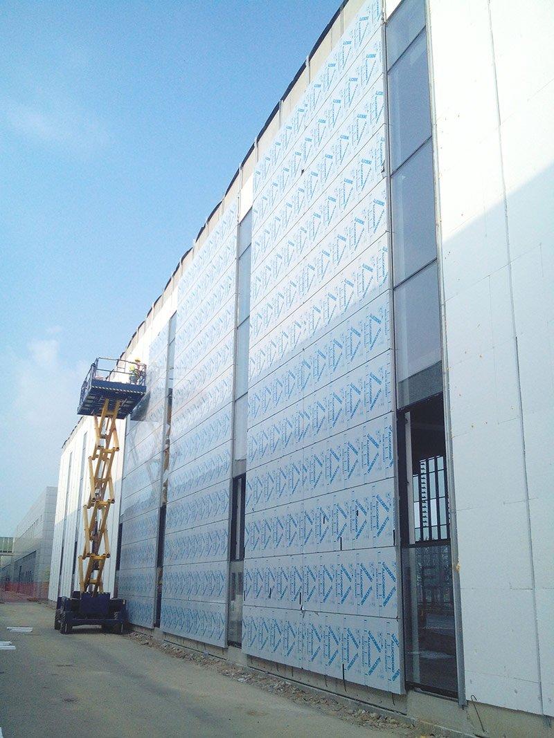 Facciata di un capannone industriale con copertura a pannelli bianchi