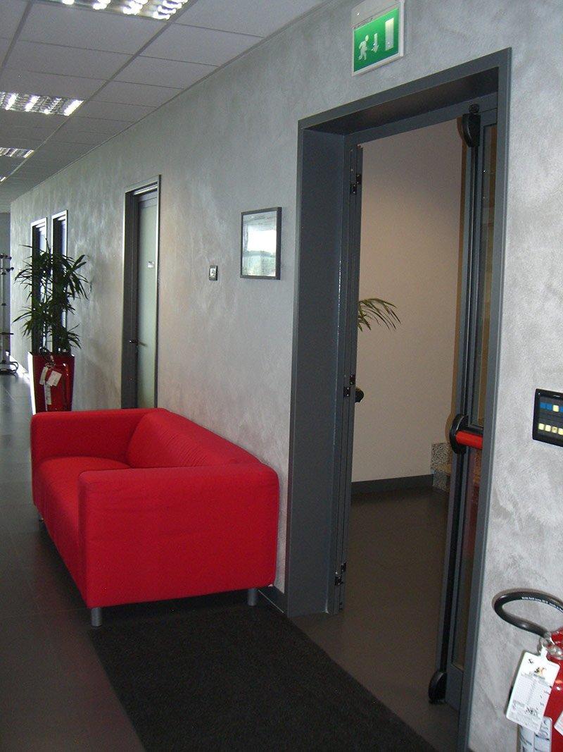 ingresso di un ufficio con divano rosso