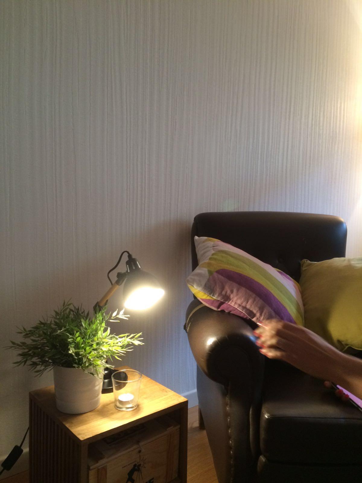 un poltrona con dei cuscini e un tavolino con lampada