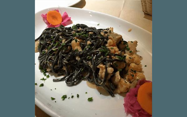 Tagliolini al nero di seppia con gamberi, salmone, scalogno, wodka, porcini e panna