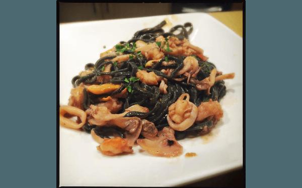 Tagliolini al nero di seppia con calamari, gamberi, frutti di mare sgusciati e pomodorini