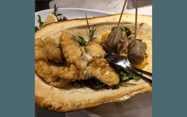 Cestino di pasta brisä, letto di insalata mista, filetti di baccalà fritto, polenta e salsicce