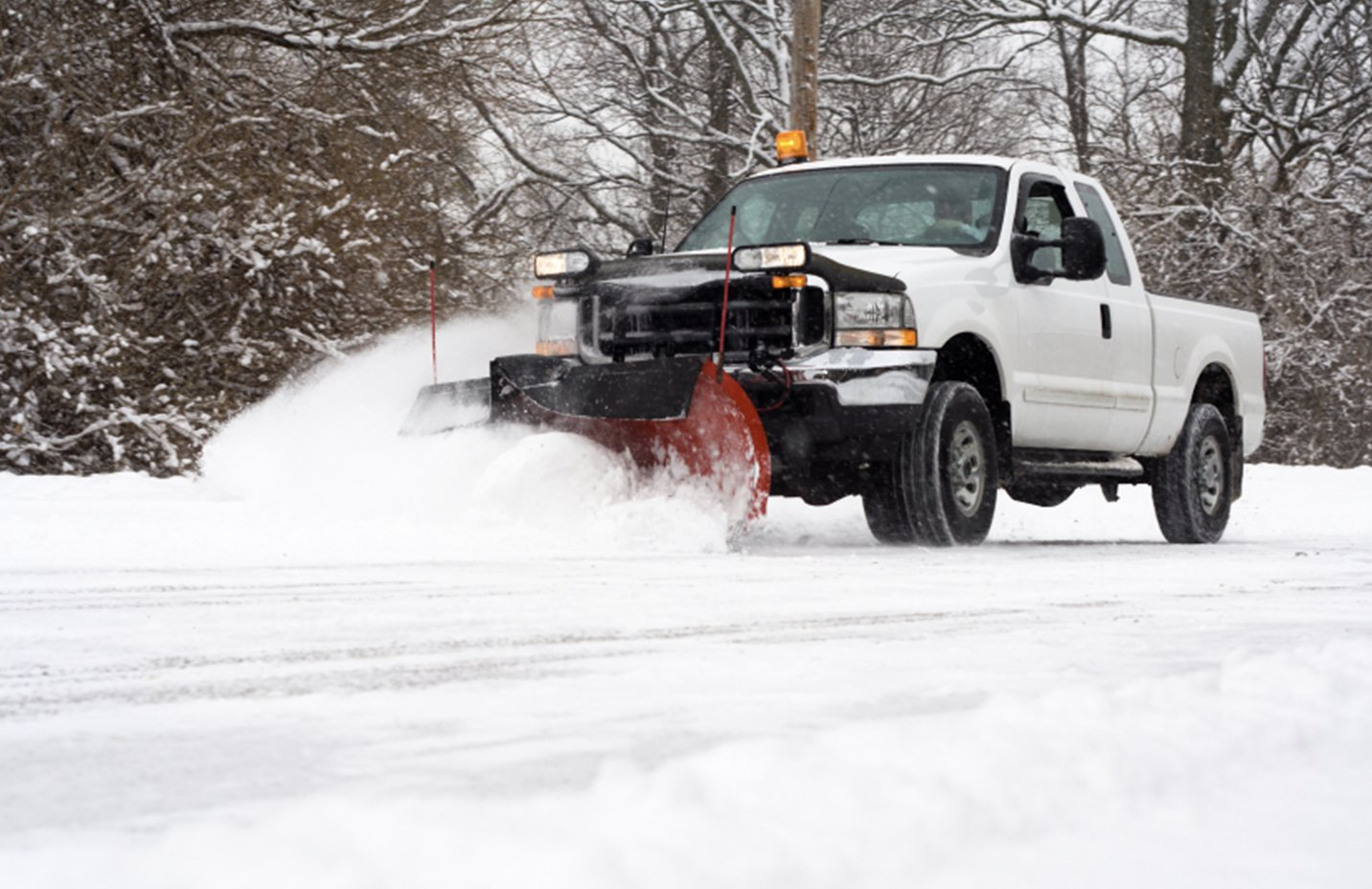 white ford truck removing snow with a front end plow