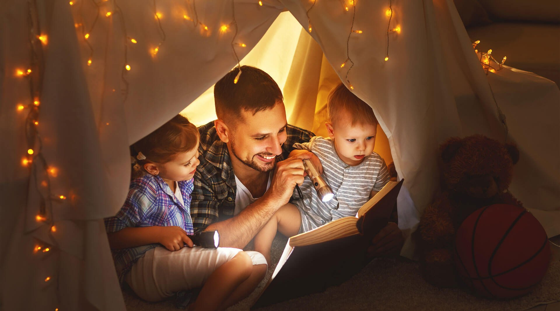 father playing with his children in a tent