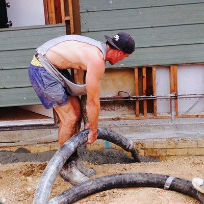 man pumping concrete to make path