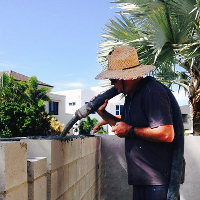 concrete worker with hat filling wall with mix