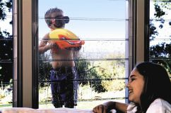 child outside window with a squirt gun