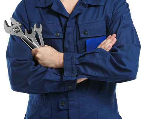 un meccanico con una tuta blu e degli utensili in mano