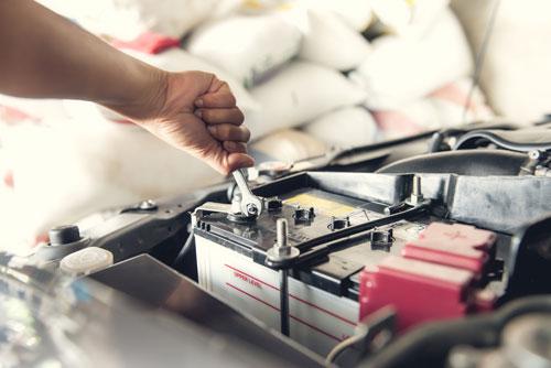 una mano con una chiave inglese che svita il bullone di una batteria di una macchina