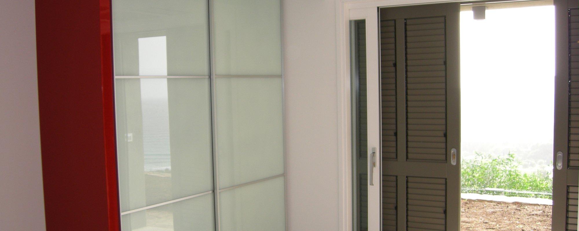 Camera da letto con armadio ad ante scorrevoli in vetro e porta finestra aperta