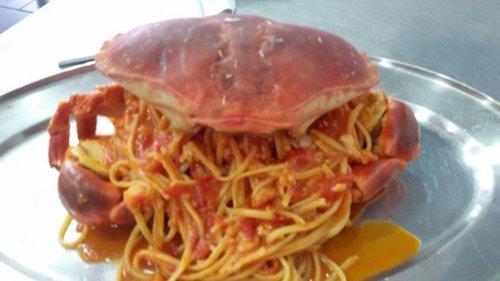 vassoio di spaghetti al sugo con grosso granchio