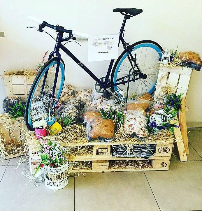 un pallet con sopra della paglia, delle confezioni di panettone,colomba e una bicicletta