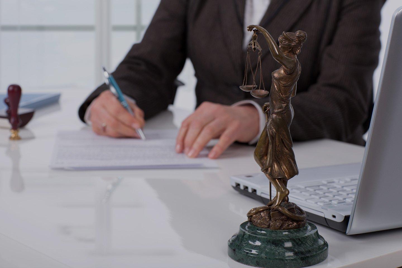 Avvocato durante la stesura di un contratto e statua della giustizia