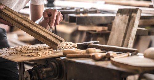 falegname che rifinisce i dettagli di una trave in legno