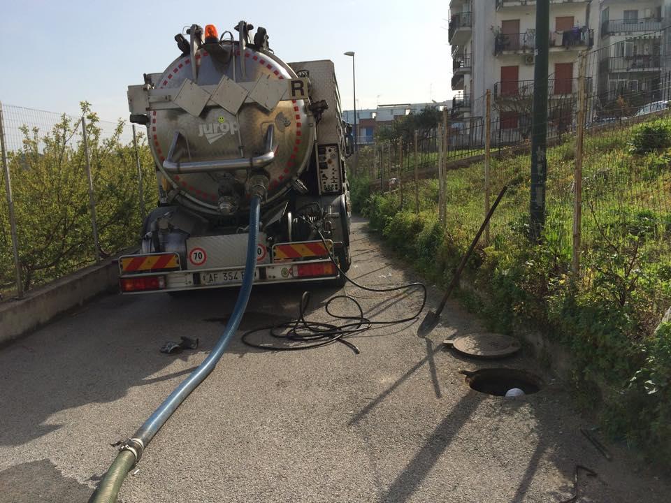 un camion degli spurghi visto da dietro con un tubo