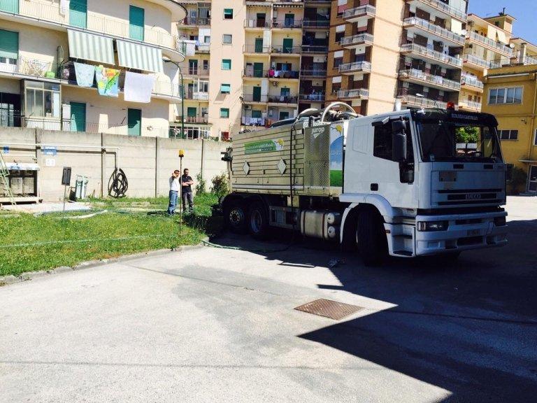due uomini e vicino un camion degli spurghi