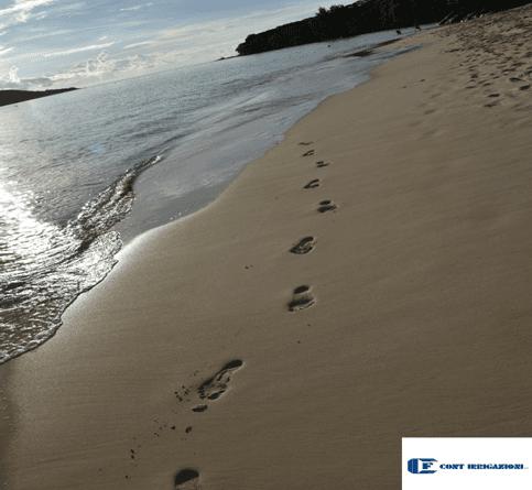 Battigia con orme di piedi sulla sabbia
