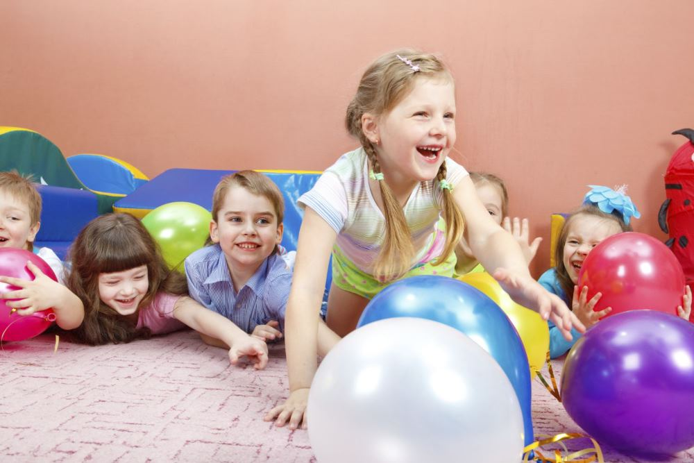 Toddlers playing with balloons at a daycare facility in Mendon, NY