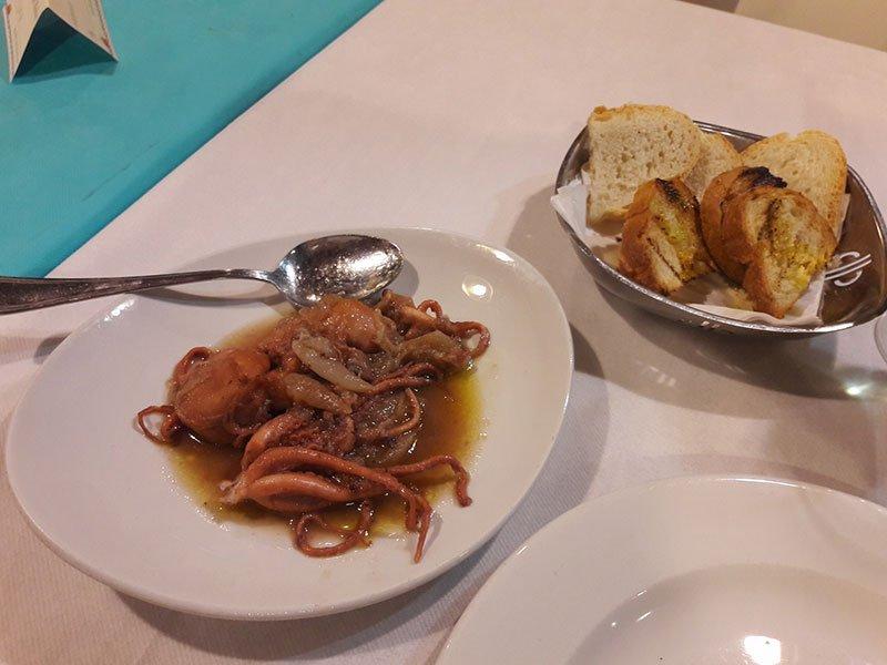 un piatto a base di seppie e un cestino di pane