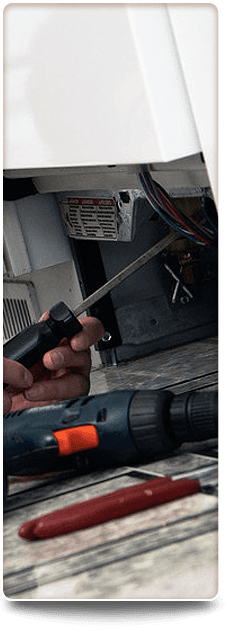 Man's hand holding a screwdriver fixing a domestic appliance