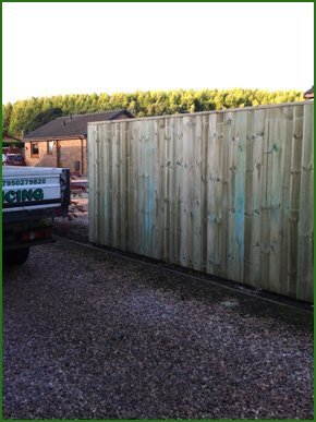 A gravel driveway and a timber fence
