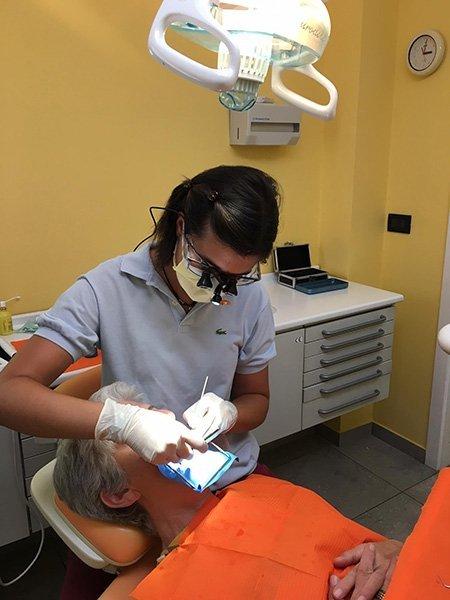 Odontoiatra che effettua un trattamento al paziente