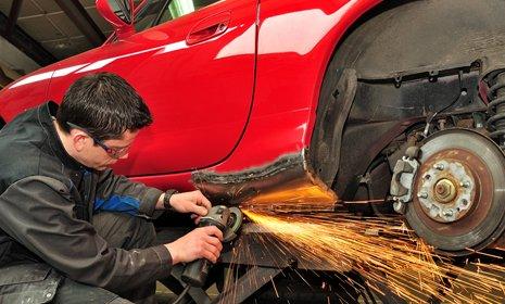 meccanico mentre usa una smerigliatrice su una carrozzeria di