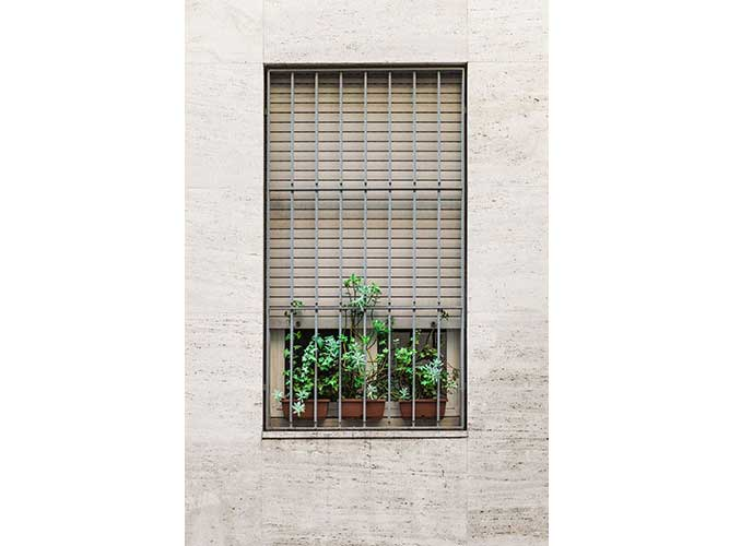 finestra con inferriate e vasi di fiori appoggiati sul davanzale