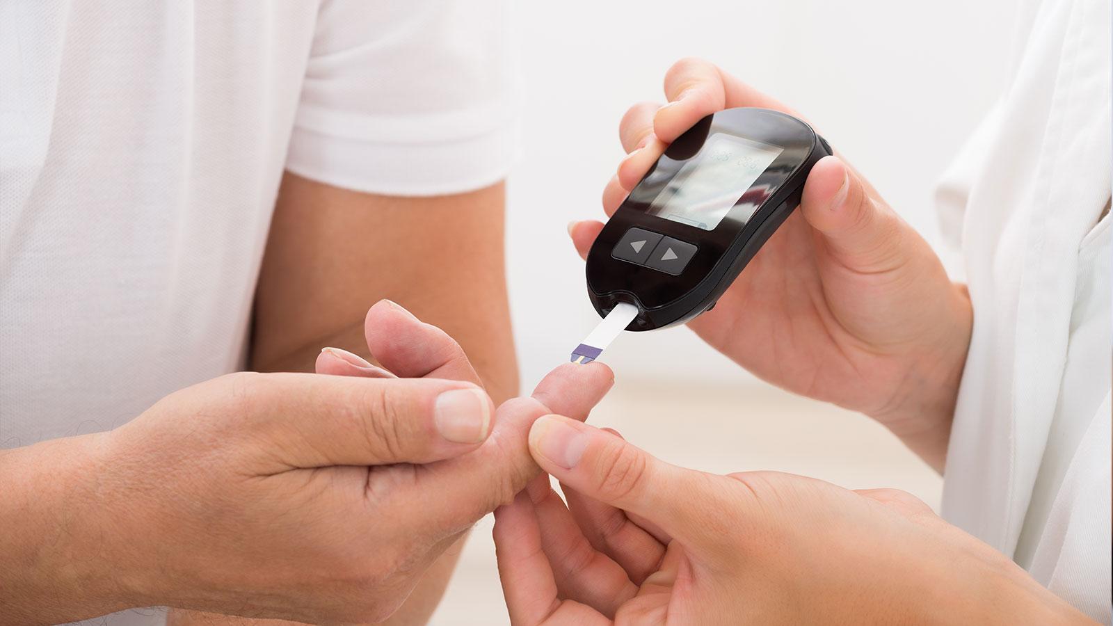 Mano del medico Utilizzando glucometro al dito di paziente
