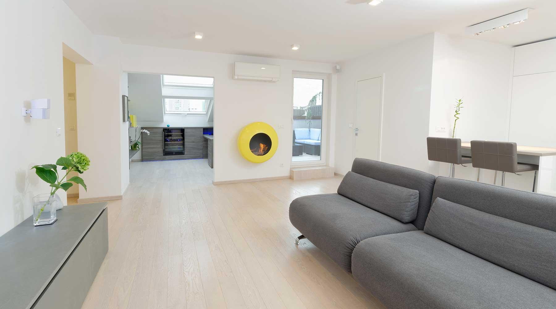 un salotto ampio e moderno con divani grigio sulla destra, a sinistra un mobile con sopra un vaso con una pianta