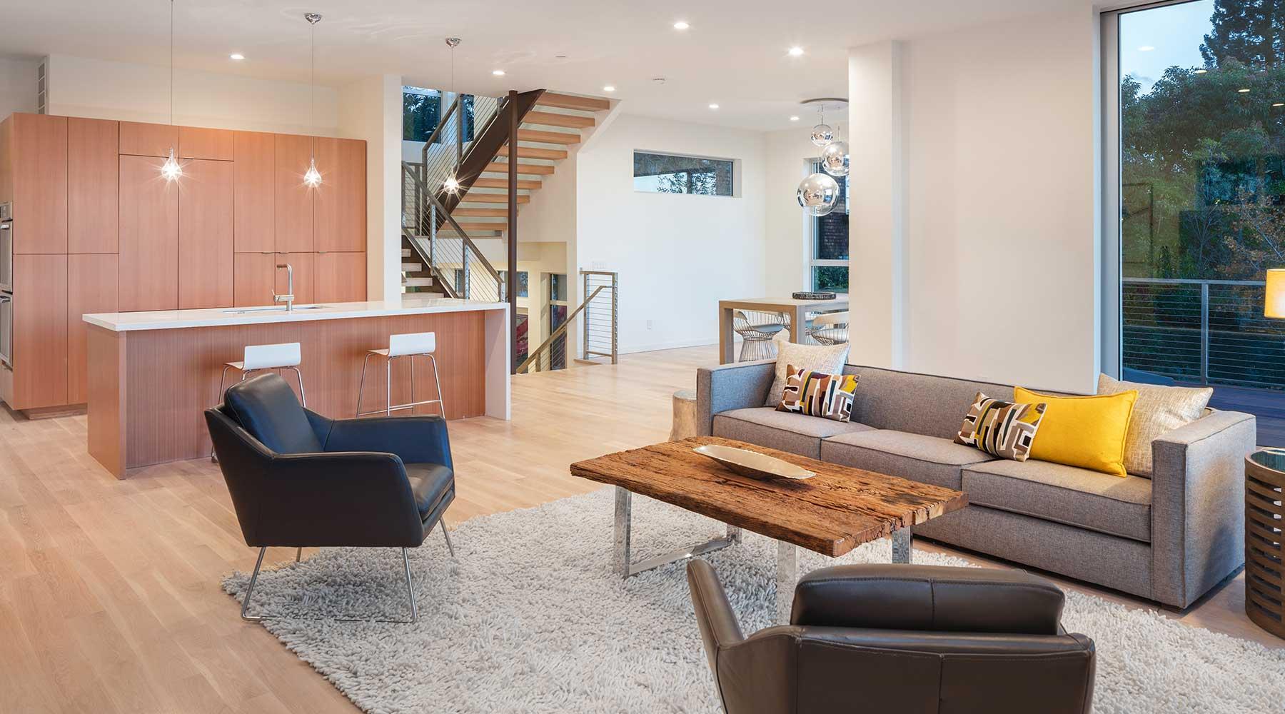 salotto moderno open space con un divano grigio, due poltrone,un tavolino rettangolare in legno in fondo una penisola in legno e vista di una scala che va al piano superiore