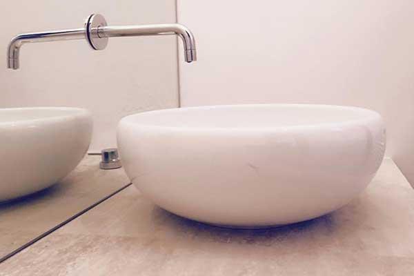 un lavabo rotondo con il rubinetto inserito in uno specchio, il tutto visto lateralmente