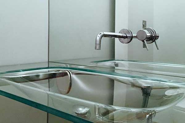 vista del rubinetto di un lavabo inserito in uno specchio e sotto un lavandino in vetro