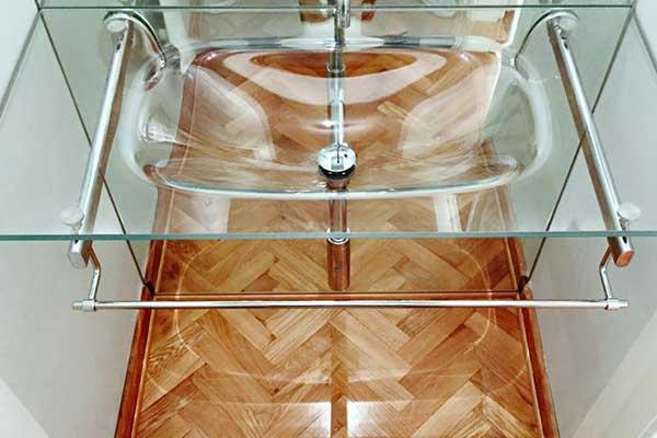 un lavabo inserito in una mensola di vetro e sotto un porta asciugamani in acciaio