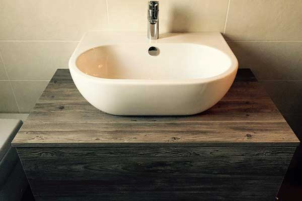 un lavabo moderno con rubinetti moderni in acciaio e sotto una mobile in legno
