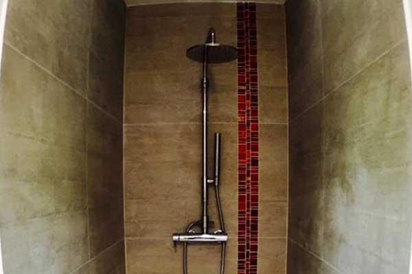 vista di un box doccia lungo e non tanto largo con tubi e doccia in acciaio e piastrelle beige