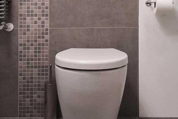 vista di un wc moderno con con pulsanti scarico in alluminio su uno sfondo di piastrelle grigie