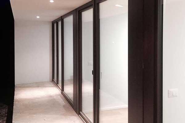 delle porte finestre scorrevoli in vetro viste lateralmente con rifiniture in legno scuro