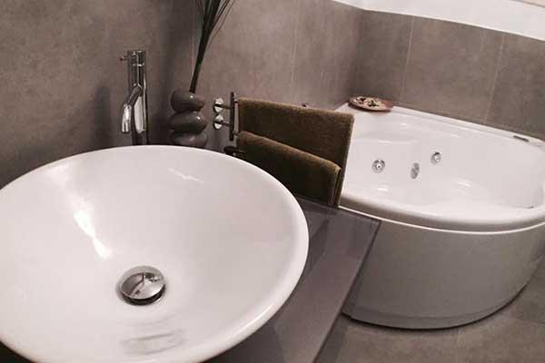 un lavabo rotondo con rubinetti in acciaio,degli asciugamani marroni su un porta asciugamani e dietro una vasca da bagno rotonda angolare