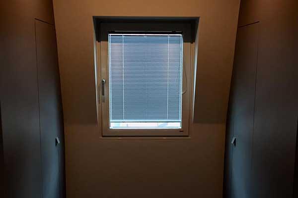 una finestrella in vetro e rifiniture in pvc con una tendina stile ufficio