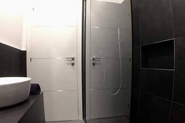 un bagno moderno con sulla sinistra un lavabo rotondo bianco, sulla destra una vetrata e il box doccia e al centro una porta di color bianco con maniglia in acciaio