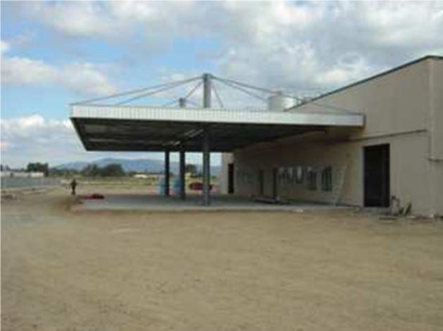 Tettoia metallica zincata con copertura tirantata. Caseificio sociale di Oristano (Sardegna).