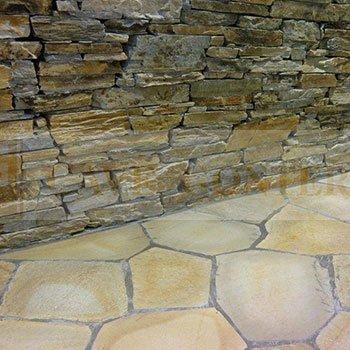 un muro in pietra e un pavimento in pietra color sabbia