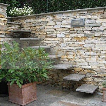 dei gradini in granito e un muro in pietra color sabbia