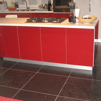 delle piastrelle nere in marmo e una penisola di una cucina di color rosso