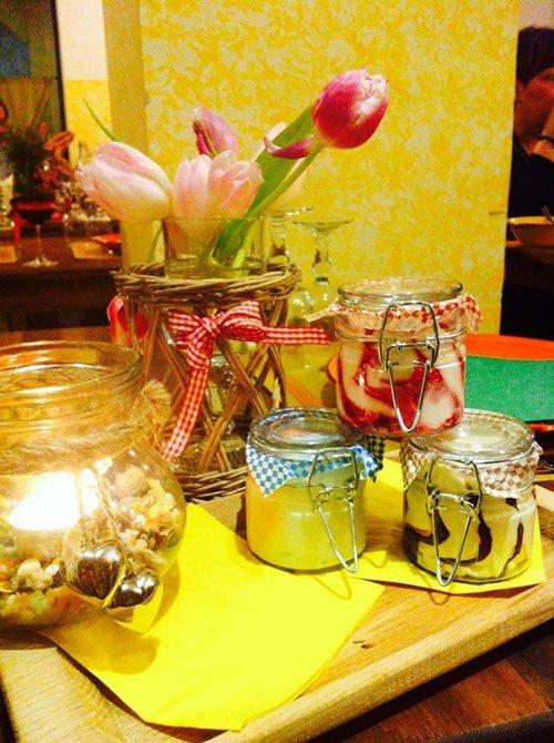 tre barattoli di mousse e accanto un vaso di fiori