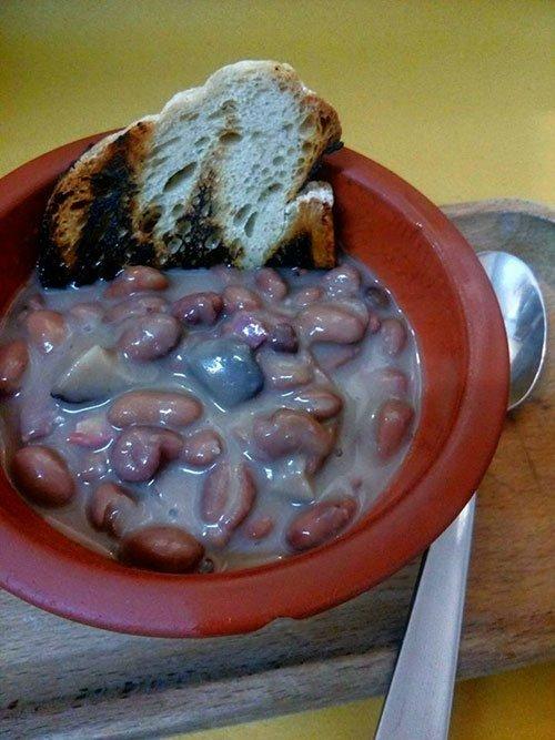 una ciotola con una zuppa di fagioli e crostini